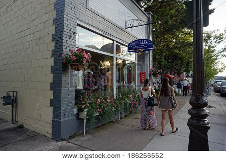 HARBOR SPRINGS, MICHIGAN / UNITED STATES - AUGUST 4, 2016: Pedestrians stroll past the Propellers boutique, which sells resort wear, gifts and accessories, on Main Street in downtown Harbor Springs.