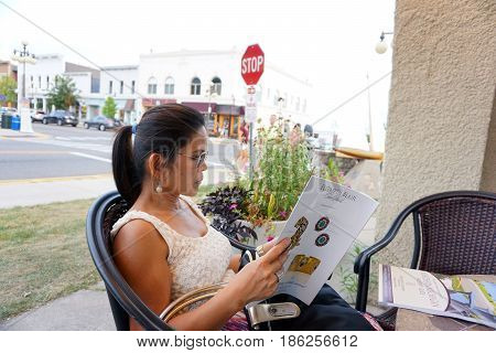 HARBOR SPRINGS, MICHIGAN / UNITED STATES - AUGUST 4, 2016: A woman sits and reads a magazine outside the Hollywood Market in downtown Harbor Springs.