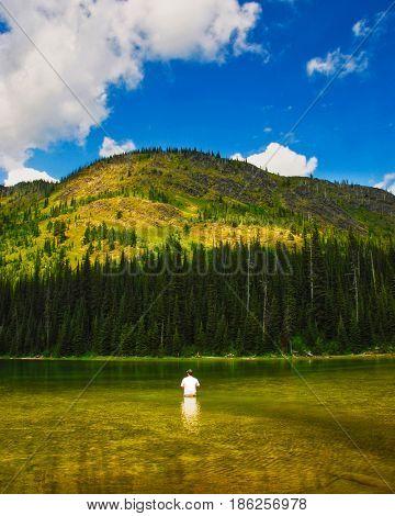 Man fishing at Moose Lake in Whitefish Range near Kalispell, Montana