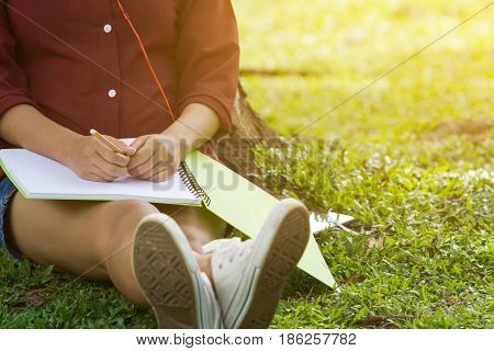 Asian women sitting under the tree with blank notebook