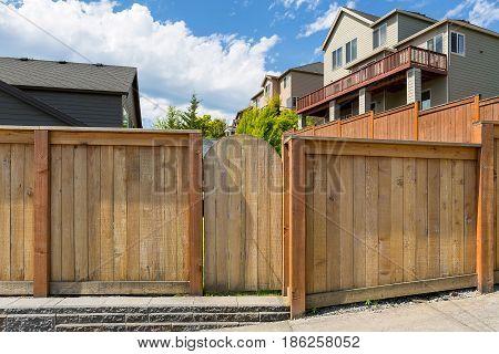 House backyard new wood fence garden gate door in suburban residential neighborhood