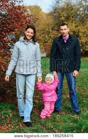 Parents Walking With His Little Daughter In Park
