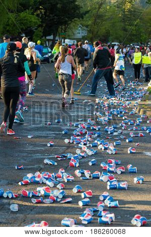 EUGENE, OR - MAY 7, 2017: Volunteers clean up cups covering the ground after runners take a drink at an aid station at the 2017 Eugene Marathon race held on the University of Oregon campus.