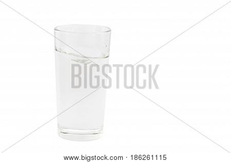 transparent glass with the clear water poured in it on a white background