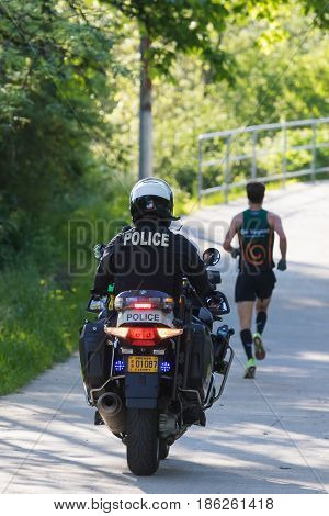 EUGENE, OR - MAY 7, 2017: Eugene Police motorcycle officer escorts the back of the eilite pack of professional runners during the 2017 Eugene Marathon race held on the University of Oregon campus.