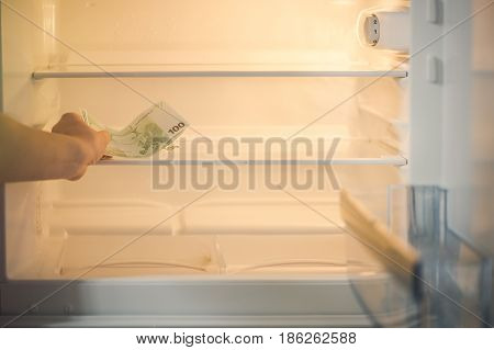 Euro banknotes in an empty refrigerator:a handful of 100 euros banknotes in an empty refrigerator. Female hand take money from fridge