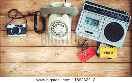 Top view hero header - retro technology of radio cassette recorder with retro tape cassette vintage telephone and film camera on wood table. Vintage color effect styles.