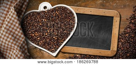 Roasted coffee beans in a heart shaped bowl and an empty blackboard with wooden frame and copy space on a table with a checkered tablecloth