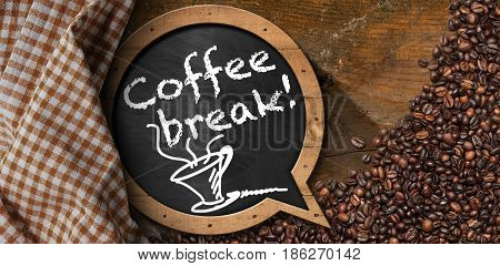 Coffee Break - Blackboard in the shape of a speech bubble with roasted coffee beans and a coffee cup. On a wood background with a checkered tablecloth