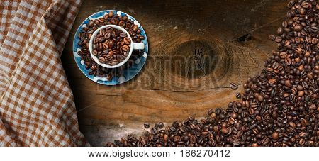 Coffee cup with roasted coffee beans on a dark wooden table with copy space and a checkered tablecloth