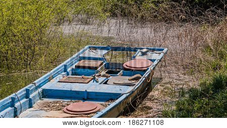 Closeup of blue fishing boat in marsh among high bushes and reeds.