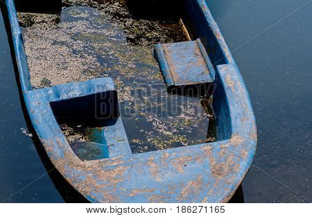 Closeup of blue fishing boat filled with dirty water floating in river