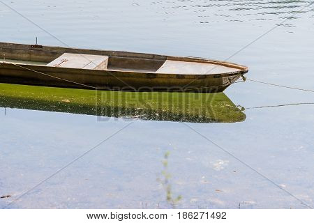 Small metal fishing boat floating in a river with its reflection in the water