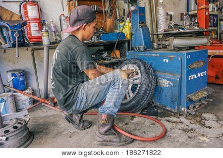 Labuan,Malaysia-May 9,2017:Car tire service mechanic changing car wheel before makes computer wheel balancing on special equipment machine tool in auto repair service in Labuan,Malaysia.