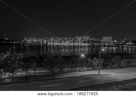 Black and white photo of city lake park in South Korea with skyline in the background taken at night.