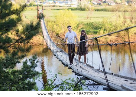 Happy young couple in love embracing each other on the suspended bridge
