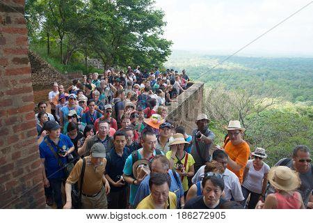 SIGIRIA, SRI LANKA - MARCH 16, 2015: Tourists stand in line waiting for climb to the top of Sigiriya mountain
