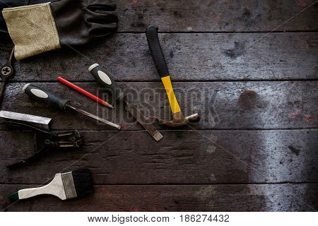 Inverted welding machine welding equipment on a wooden desk with workshop background welding mask leather gloves welding electrodes high-voltage wires with clips set of accessories for arc welding.