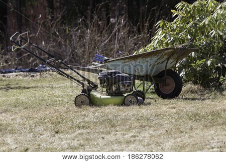 A Wheelbarrow and a Lawnmower in Garden.