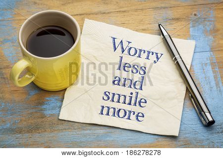 Worry less and smile more - handwriting on a napkin with a cup of espresso coffee