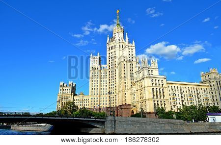 A beautiful large building from the epoch of the last century adorns the capital city, next to it flows a river through which a beautiful bridge is thrown.