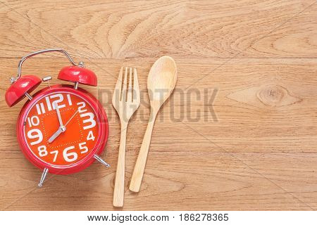 Red Alarm Clock In Wooden Dish, Spoon And Fork On Wooden Plank Background. Time Eating Concept