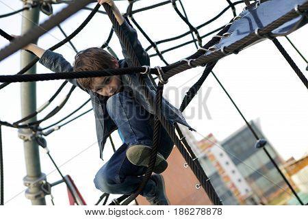 Child At Playground Climbing Net