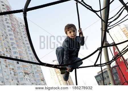 Kid At Playground Climbing Net