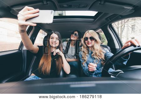 Group Of Girls Having Fun In The Car And Taking Selfies With Camera