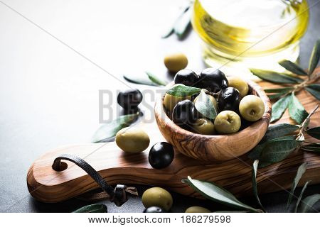 Fresh olives and olive oil in bottle. Black and green olives in wooden olive bowl. Copy space.