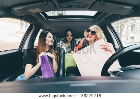 Three Women Have Fun In The Car After Shoping And Demonstrate New Buy Shoes