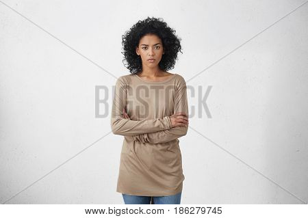 Indoor Studio Shot Of Angry Young Dark-skinned Housewife In Casual Clothes Standing In Closed Postur