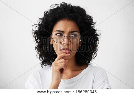Doubtful Young Woman Wearing Trendy Round Eyeglasses Frowning And Looking Sideways With Indecisive A