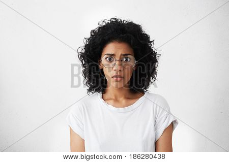 Studio Shot Of Frightened Bug-eyed Young Female Feeling Scared And Shocked, Watching Horror Movie. A