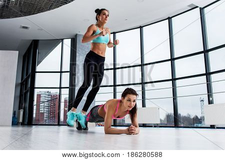 Young fit female athletes working-out in pair, girl jumping over her friend while woman performing plank position