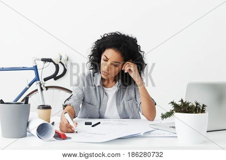 Concentrated Mixed Race Female Chief Architect Feeling Frustrated, Sitting At White Desk And Correct