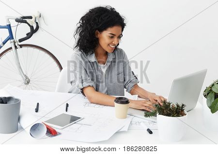 Candid Shot Of Confident Successful Skilled Female Architect Wearing Stylish Grey Shirt Over White T