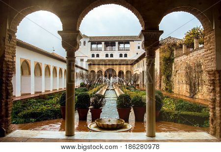 Granada, Spain - February 10, 2015: An Archway To Patio With Fountains And Cutted Brushes At General