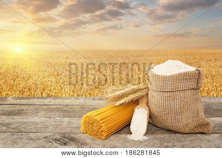 bunch of spaghetti from durum wheat, wholegrain flour in bag and scoop on table with ripe cereal field on the background. Photo with place for text. Golden wheat field on sunset