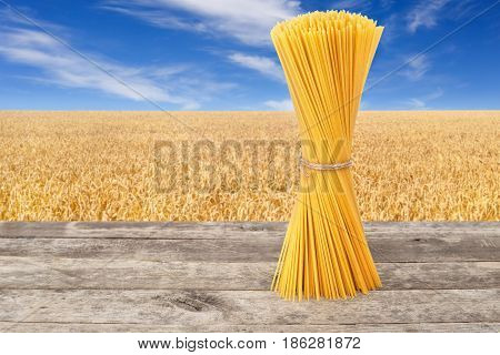 bundle of uncooked spaghetti from durum wheat on table with ripe cereal field on the background.  Golden wheat field with blue sky. Healthy eating. Photo with place for text