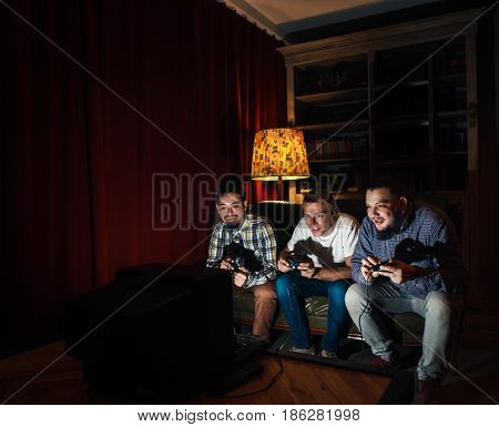 Three young guys sit on couch with joysticks addicted to video game. Excessive play, addiction, psychological disorder, illness, unhealthy lifestyle concept