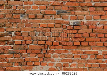 Old brick wall of red brick with uneven rows