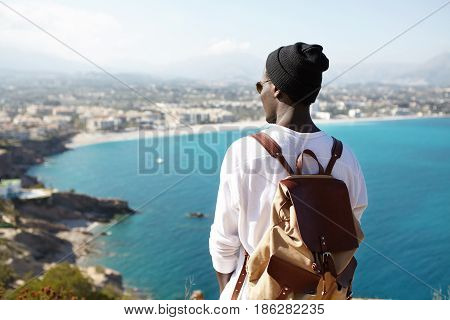 Rear View Portrait Of Young African American Backpacker Facing Sea Standing On Viewing Platform Or R