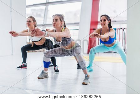Young slim women in sportswear doing squat exercise during intensive circuit training in sporty.