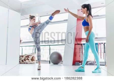 Young Caucasian woman training with a personal trainer in gym practicing high side kicks