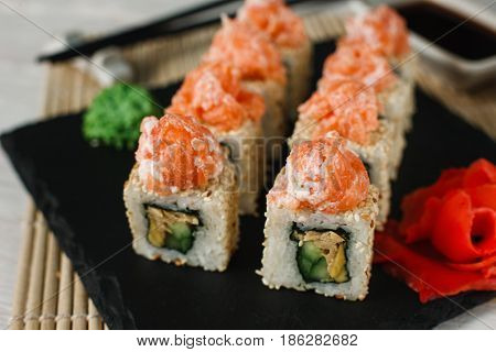 Appetizing and fresh set of sushi uramaki rolls served on black slate, close up. Traditional Asian food, Japanese healthy seafood.