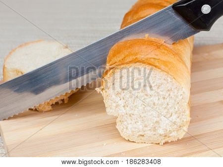 a loaf of homemade bread and a slice on a wooden breadboard with a bread knife.