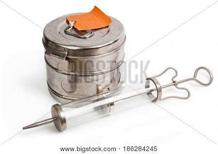 Steam sterilizer and large syringe with thick needle isolated on white