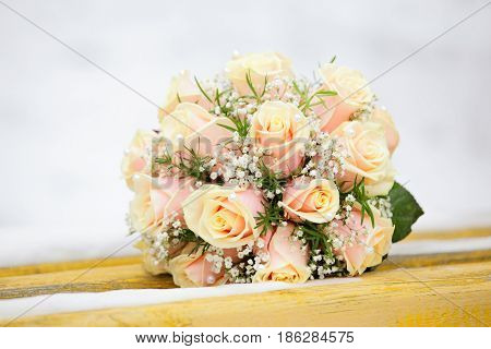 beautiful bouquet of the bride executed from light beige roses and lie on the snow bench