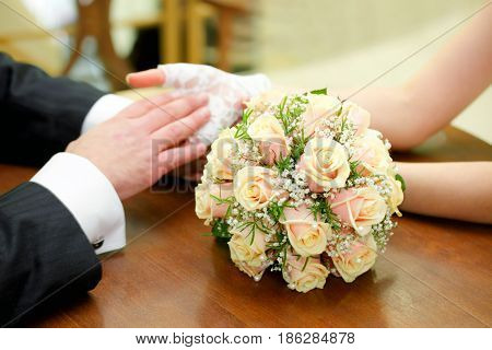 Hands with rings and wedding bouquet on the table